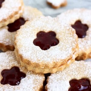 Six gluten-free vegan linzer cookies filled with raspberry jam