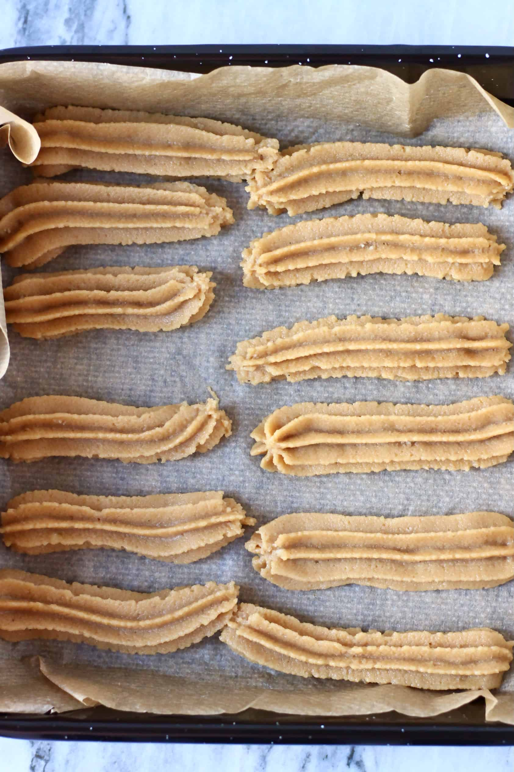 Twelve raw gluten-free vegan churros piped out onto a baking tray lined with baking paper