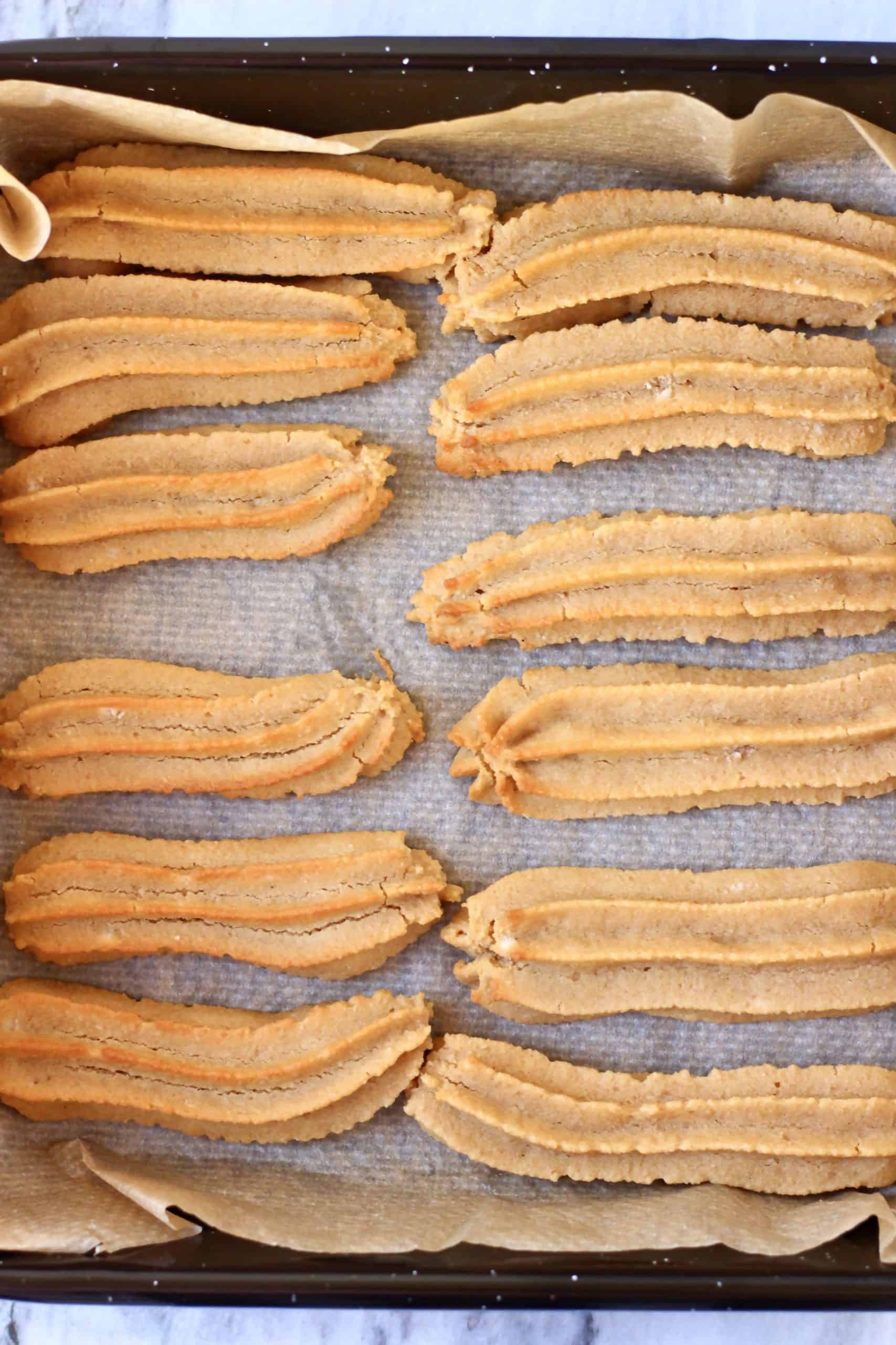 Twelve baked gluten-free vegan churros on a baking tray lined with baking paper