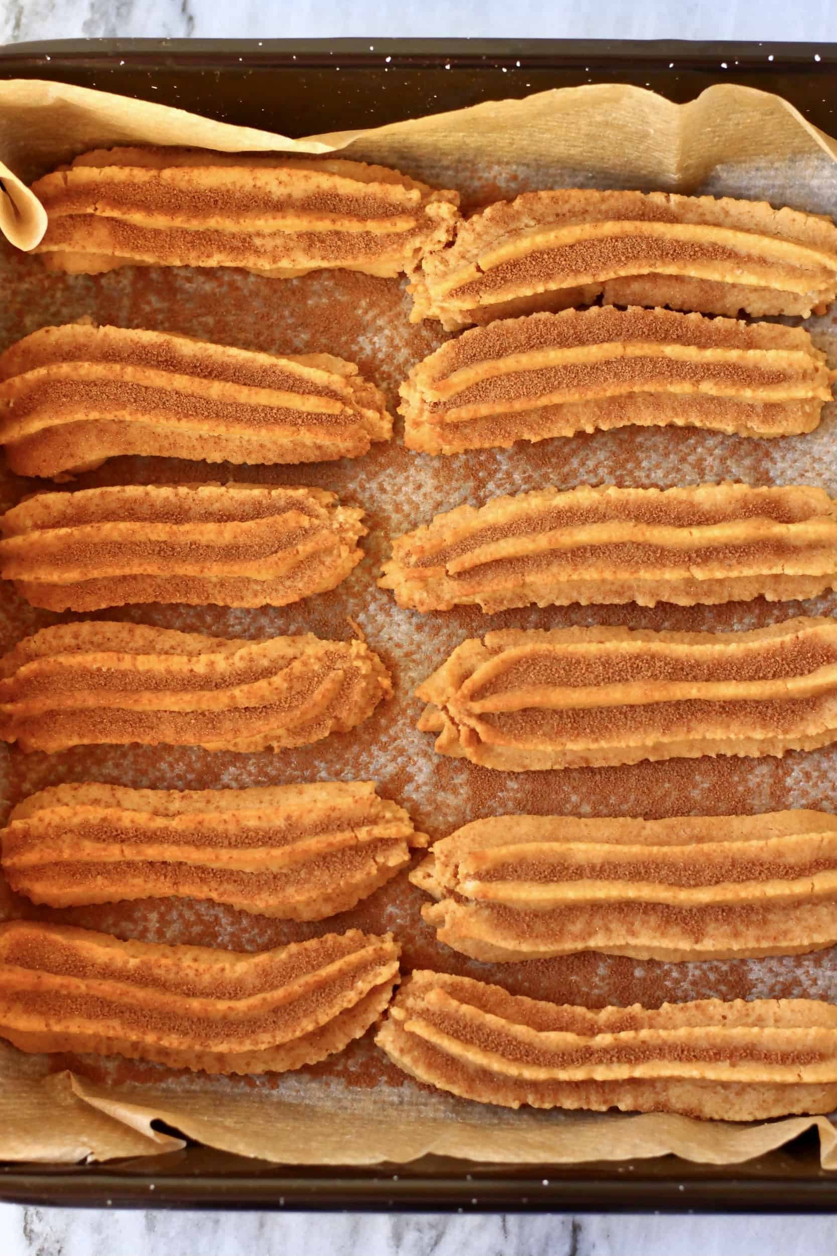 Twelve baked gluten-free vegan churros dusted with cinnamon sugar on a baking tray