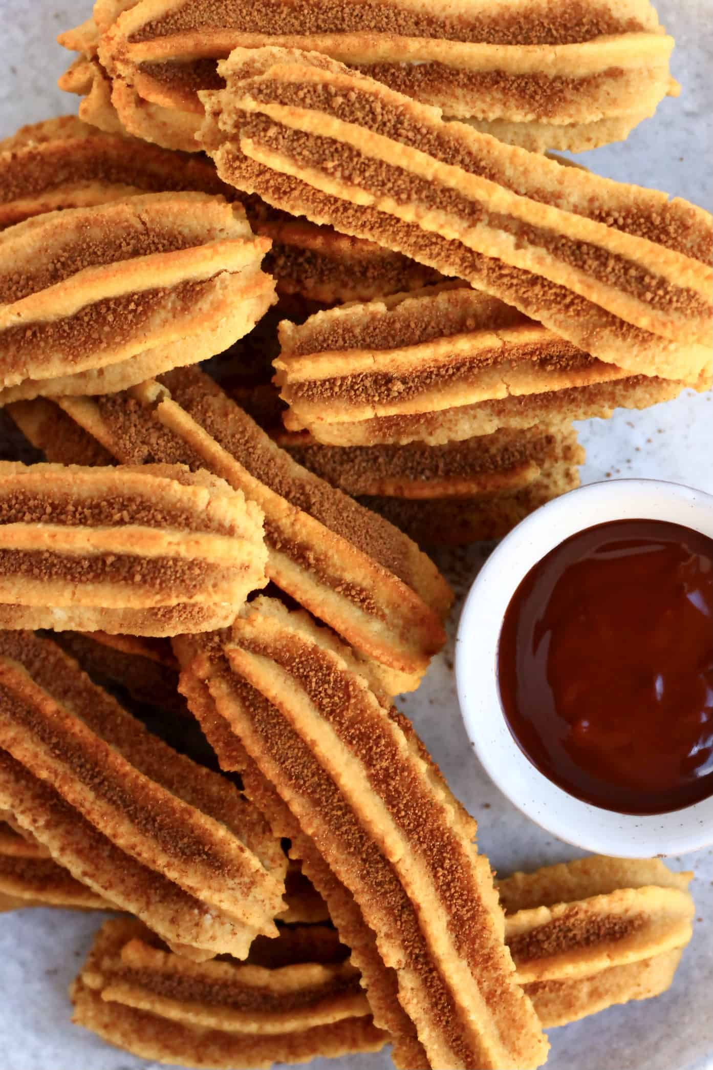 Several gluten-free vegan churros dusted with cinnamon sugar on a plate with a bowl of vegan chocolate sauce